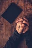 Manos dobladas del hombre cristiano que ruegan Foto de archivo