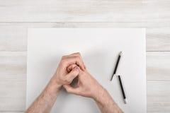 Manos dobladas masculinas del primer en el panel de madera con el Libro Blanco y el lápiz negro roto en la visión superior fotos de archivo