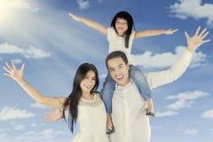 Manos emocionadas del aumento de la familia para arriba al aire libre Fotografía de archivo
