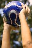 Manos en balón de fútbol en el cielo Foto de archivo
