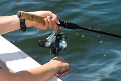Manos en carrete de la pesca Fotos de archivo