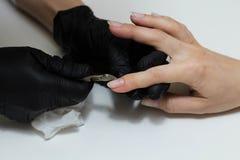 Manos en cuidados negros de los guantes sobre clavos de las manos Sal?n de belleza de la manicura Limadura de clavos con el fiche fotografía de archivo libre de regalías