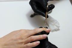 Manos en cuidados negros de los guantes sobre clavos de las manos Sal?n de belleza de la manicura Limadura de clavos con el fiche imagen de archivo libre de regalías