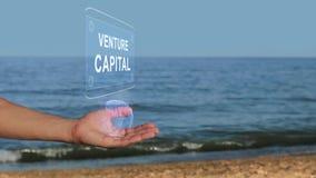 Manos en el capital de riesgo del texto del holograma del control de la playa almacen de metraje de vídeo