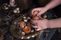 Manos en el marco, huevos del ` s de los niños de Pascua grandes y pequeños, plumas Foto en estilo del vintage Accesorios rurales Fotos de archivo