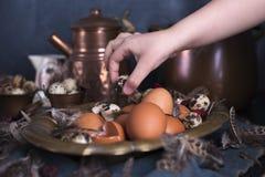 Manos en el marco, huevos del ` s de los niños de Pascua grandes y pequeños, plumas Foto en estilo del vintage Accesorios rurales Imagen de archivo
