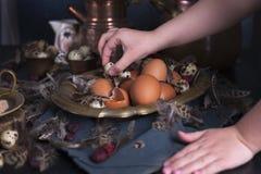 Manos en el marco, huevos del ` s de los niños de Pascua grandes y pequeños, plumas Foto en estilo del vintage Accesorios rurales Foto de archivo