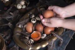 Manos en el marco, huevos del ` s de los niños de Pascua grandes y pequeños, plumas Foto en estilo del vintage Accesorios rurales Imágenes de archivo libres de regalías