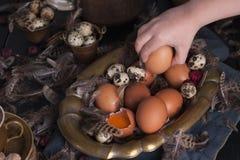 Manos en el marco, huevos del ` s de los niños de Pascua grandes y pequeños, plumas Foto en estilo del vintage Accesorios rurales Fotografía de archivo libre de regalías