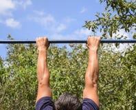 Manos en el primer de la barra El hombre se tira para arriba en la barra Jugar deportes en el aire fresco Barra horizontal Foto de archivo