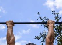 Manos en el primer de la barra El hombre se tira para arriba en la barra Jugar deportes en el aire fresco Barra horizontal Fotos de archivo libres de regalías