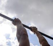Manos en el primer de la barra El hombre se tira para arriba en la barra Jugar deportes en el aire fresco Barra horizontal Imagen de archivo