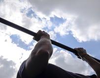 Manos en el primer de la barra El hombre se tira para arriba en la barra Jugar deportes en el aire fresco Barra horizontal Imágenes de archivo libres de regalías
