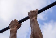 Manos en el primer de la barra El hombre se tira para arriba en la barra Jugar deportes en el aire fresco Barra horizontal Foto de archivo libre de regalías