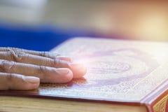Manos en el Quran imagen de archivo