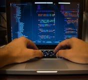 Manos en el teclado de la computadora portátil Hombre en la codificación foto de archivo libre de regalías