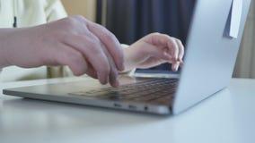 Manos en el teclado del ordenador portátil moderno Fingeres que mecanografían el texto almacen de metraje de vídeo