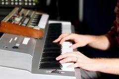 Manos en el teclado del órgano eléctrico Foto de archivo