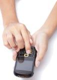 Manos en el teléfono celular que pulsa SMS Imagen de archivo libre de regalías