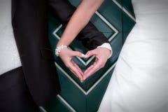 Manos en forma de corazón de la novia y del novio en la boda imagen de archivo
