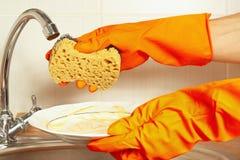Manos en guantes con la esponja y platos sucios sobre el fregadero en cocina Imagenes de archivo
