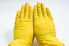 Manos en guantes de goma amarillos en el fondo blanco Foto de archivo