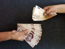 manos en intercambio de moneda, cuentas mexicanas y notas euro Imagen de archivo