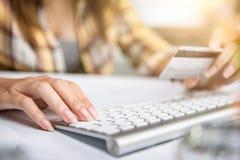 Manos en línea que hacen compras de la mujer que sostienen la tarjeta de crédito y que usan el ordenador portátil Foto de archivo libre de regalías