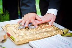Manos en la biblia en una boda Fotografía de archivo libre de regalías