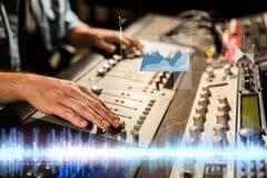 Manos en la consola de mezcla en el estudio de grabación de los sonidos foto de archivo