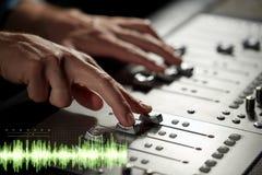 Manos en la consola de mezcla en el estudio de grabación de los sonidos imagen de archivo libre de regalías