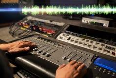 Manos en la consola de mezcla en el estudio de grabación de los sonidos fotografía de archivo