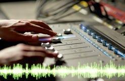 Manos en la consola de mezcla en el estudio de grabación de la música imágenes de archivo libres de regalías