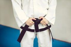 Manos en la correa negra y el kimono el arte marcial de Tae Kwon hace y karate fotos de archivo