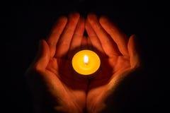 Manos en la forma de un corazón que lleva a cabo una vela encendida en un negro Fotos de archivo libres de regalías