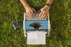 Manos en la máquina de escribir al aire libre Fotos de archivo