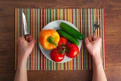 Manos en la tabla con las verduras Imagen de archivo libre de regalías
