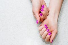 Manos en la tabla con la manicura Clava la púrpura, rosa imagenes de archivo