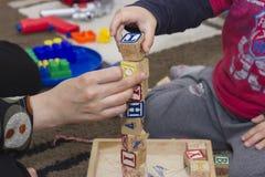 Manos en los cubos de madera foto de archivo libre de regalías