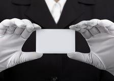 Manos en los guantes blancos que sostienen la tarjeta plástica Fotos de archivo libres de regalías
