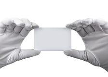 Manos en los guantes blancos que sostienen una tarjeta plástica blanca en un fondo blanco Fotos de archivo
