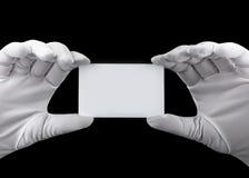 Manos en los guantes blancos que sostienen una tarjeta plástica blanca en un fondo negro Fotos de archivo libres de regalías