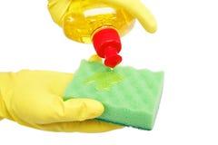 Manos en los guantes de goma con una botella y una esponja Imagen de archivo