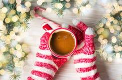 Manos en los guantes del invierno que sostienen una taza de café Fotos de archivo