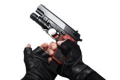 Manos en los guantes que recargan el arma Imagenes de archivo