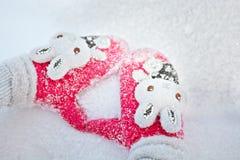 Manos en manopla roja en fondo de la nieve. Imagen de archivo libre de regalías