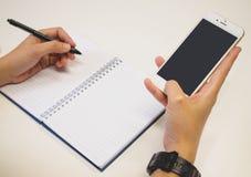 Manos en pluma y con smartphone al mismo tiempo imagenes de archivo