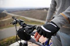Manos en un manillar de la bici Foto de archivo