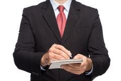 Manos en un traje de negocios que sostiene una pluma Imagen de archivo libre de regalías