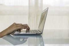 Manos en una computadora portátil Imagen de archivo libre de regalías